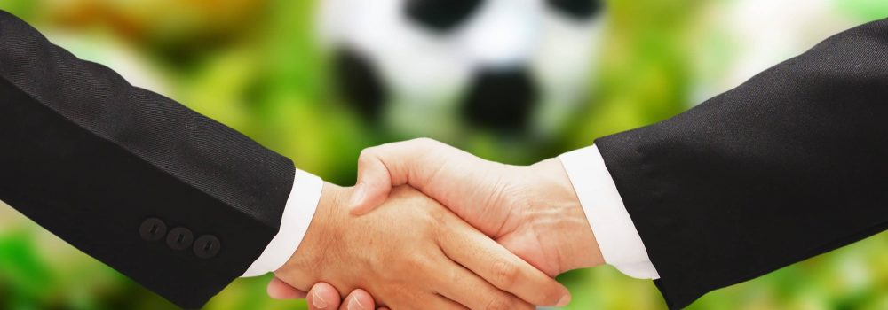 business man hand shake with soccer blur background
